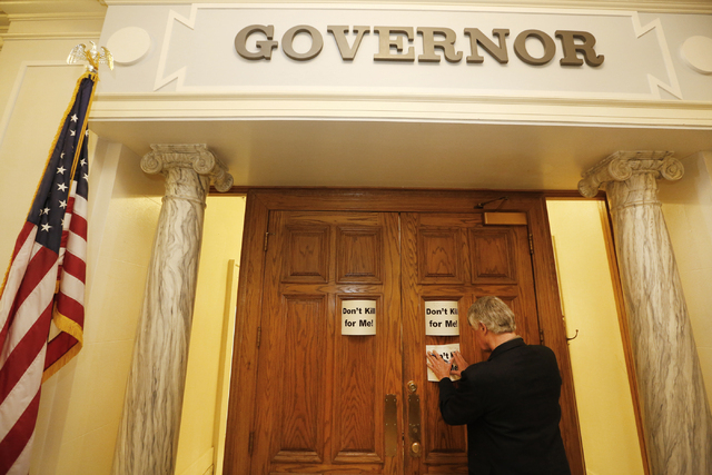 Nathaniel Batchelder, with the Oklahoma Coalition Against the Death Penalty, places a sign protesting the death penalty on Gov. Mary Fallin's office at the state Capitol in Oklahoma City on Tuesda ...