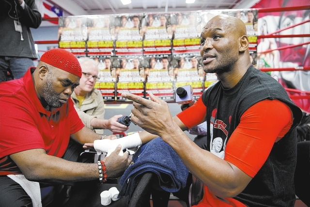 IBF light heavyweight boxing champion Bernard Hopkins speaks with reporters as  trainer Naazim Richardson, left, tapes his hands during a media workout Thursday, April 10, 2014, in Philadelphia. H ...