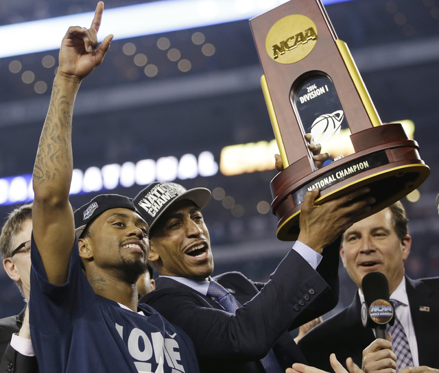 Connecticut head coach Kevin Ollie, center, celebrates with his team after their 60-54 victory over Kentucky in the NCAA Final Four tournament college basketball championship game Monday, April 7, ...