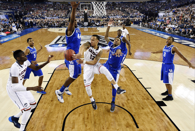 Connecticut guard Shabazz Napier (13) passes around Kentucky center Dakari Johnson (44) to center Amida Brimah (35) as guard James Young (1) helps during the first half of the NCAA Final Four tour ...