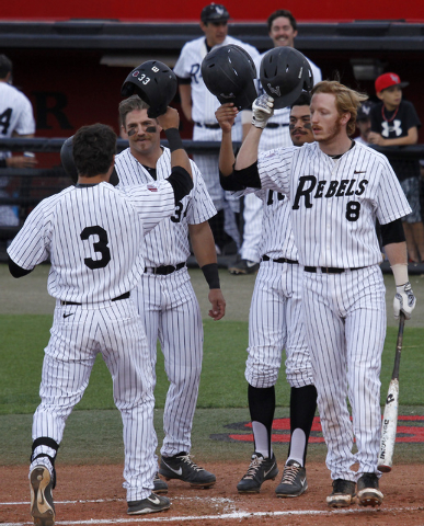 UNLV's Joey Armstrong (3) gets congratulated by teammates Patrick Armstrong (34), Edgar Montes (26) and Erik VanMeetren (8) after hitting a home run in the first inning against New Mexico during t ...