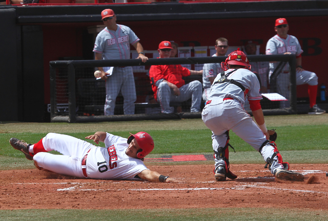 UNLV's T.J. White (10) slides into home past New Mexico catcher Lane Milligan in the third inning during a baseball game at Earl E. Wilson Stadium in Las Vegas on Sunday, April 27, 2014. UNLV won  ...