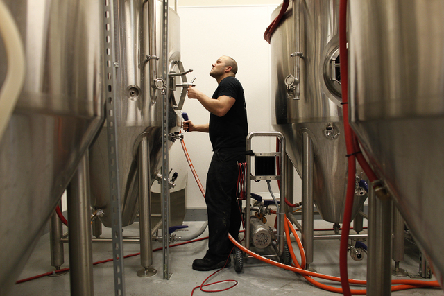 Marc Longwith closes up a fermenter after cleaning it in the brewery at Banger Brewing in downtown Las Vegas on April 4. (John Locher/Las Vegas Review-Journal)
