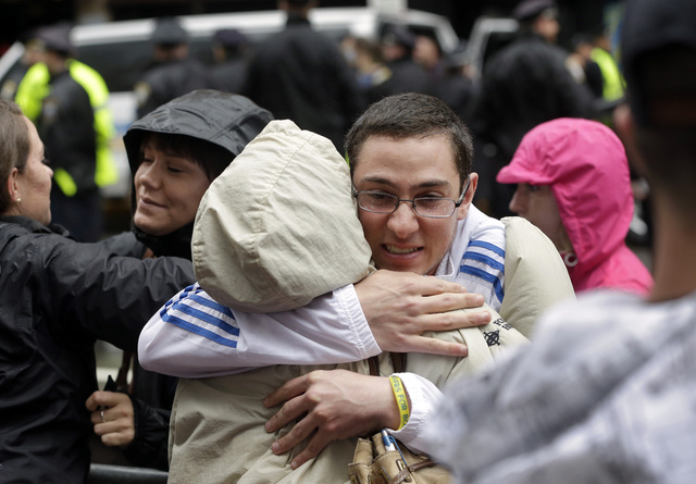 Alex Fusco, of North Reading, Mass., right, hugs his mother, Ernestine Fusco at the conclusion of tribute ceremonies near the finish line of the Boston Marathon, Tuesday, April 15, 2014, in Boston ...