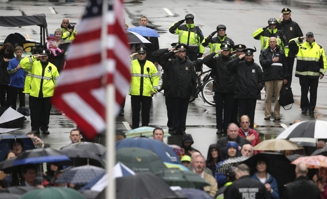Police salute as a U.S. flag is raised at the finish line during a tribute in honor of the one year anniversary of the Boston Marathon bombings, Tuesday, April 15, 2014 in Boston. (AP Photo/Charle ...