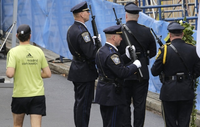 A runner passes as Boston Police honors change their post outside the Marathon Sports store, the site of the first of two bombs that exploded near the finish line of the 2013 Boston Marathon, Tues ...