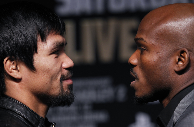 Fighters Timothy Bradley, right, and Manny Pacquiao face-off during a press conference prior to their rematch at the MGM Grand in Las Vegas on April 9, 2014. (Jason Bean/Las Vegas Review-Journal)