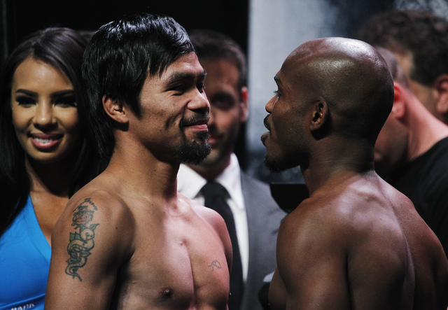Boxers Manny Pacquiao, left, and Timothy Bradley face off after getting weighed in prior to their rematch at the MGM Grand Garden Arena in Las Vegas on April 11, 2014. (Jason Bean/Las Vegas Review ...
