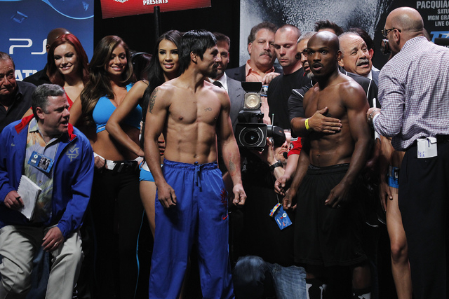 Boxers Manny Pacquiao, middle, and Timothy Bradley, right, get separated after the weigh in prior to their rematch at the MGM Grand Garden Arena in Las Vegas on April 11, 2014. (Jason Bean/Las Veg ...