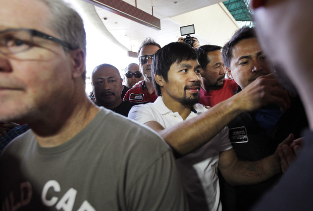 Boxer Manny Pacquiao, middle, signs autographs as he and his trainer Freddie Roach, left, arrive at the MGM Grand in Las Vegas on April 8, 2014. (Jason Bean/Las Vegas Review-Journal)
