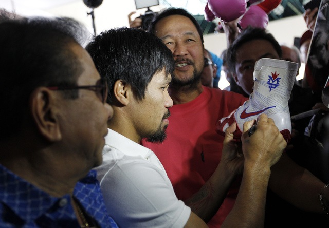 Boxer Manny Pacquiao, middle, signs autographs as he arrives at the MGM Grand in preparation for his rematch against Timothy Bradley in Las Vegas on April 8, 2014. (Jason Bean/Las Vegas Review-Jou ...