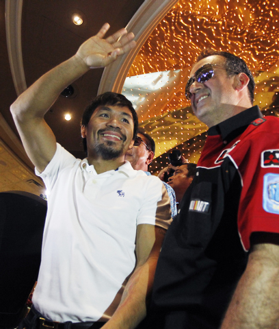 Boxer Manny Pacquiao, left, waves to his fans after arriving at the MGM Grand in preparation of his rematch against Timothy Bradley in Las Vegas on April 8, 2014. (Jason Bean/Las Vegas Review-Journal)