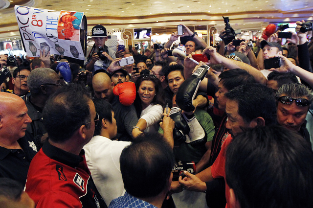 Boxer Manny Pacquiao, middle in white, signs autographs after arriving at the MGM Grand in Las Vegas on April 8, 2014. (Jason Bean/Las Vegas Review-Journal)