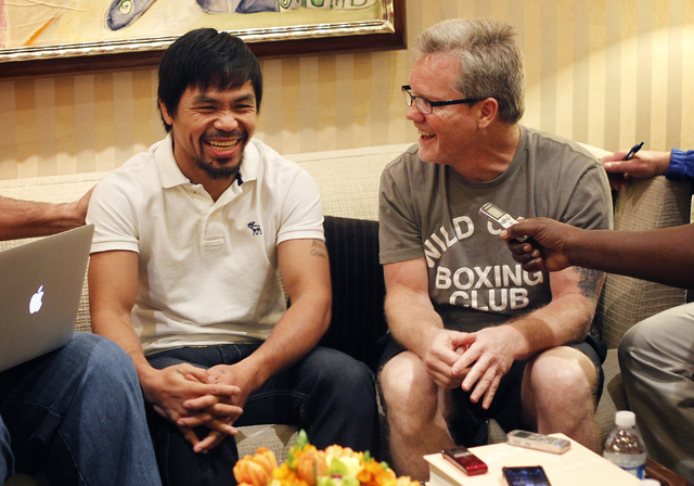 Boxer Manny Pacquiao, left, and his trainer Freddie Roach speak to the media after arriving at the MGM Grand in preparation for their rematch against Timothy Bradley in Las Vegas on April 8, 2014. ...