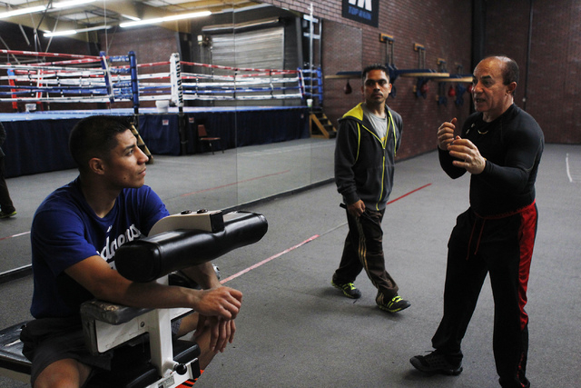 Boxer Jessie Vargas, left, prepares for his upcoming WBA junior welterweight title fight against Khabib Allakhverdiev with his trainer Ismael Salas, far right, at the Top Rank Gym in Las Vegas on  ...
