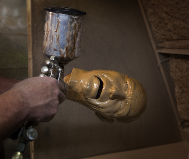 Tom Canterbury spray-paints an animatronic face. (Jeff Scheid/Las Vegas Review-Journal)