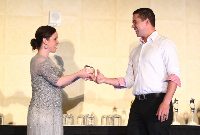 Tyler Wistisen of Blue Heron accepts the award for best living space or architectural feature for the New American Home from Ashley Helgerson during the Silver Nugget Award. (Chase Stevens/Las Veg ...