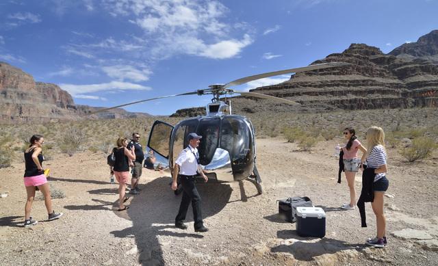 Pilot Chris Densmore, center, prepares to fly back to Las Vegas with passengers, from left, Sophie Balkin, Jules Bowen, John Brooks, Kate Balkin and Zoe Williams after a Sundance Helicopters champ ...