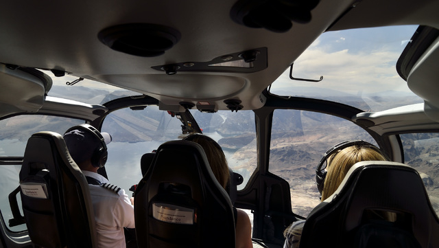 Pilot Chris Densmore, left, flies over Lake Mead with passengers Jules Bowen, center, and Zoe Williams after a Sundance Helicopters champagne lunch at the Grand Canyon on April 11. (Bill Hughes/La ...