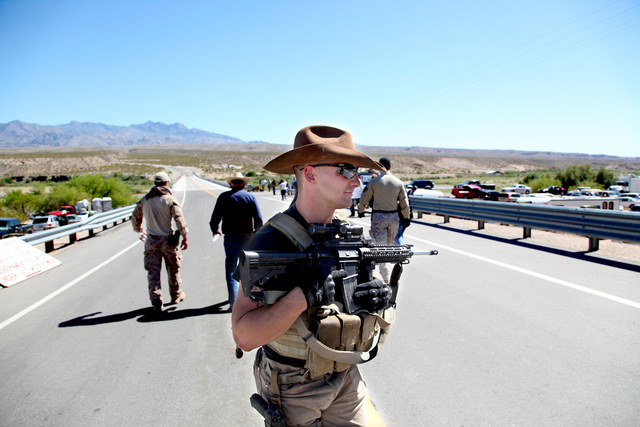 Darin Stanley, of St. George, Utah, stands guard behind Cliven Bundy as Bundy walks down Highway 170 to do an interview with Sean Hannity near Bundy's ranch in Bunkerville on Monday, April 14, 201 ...