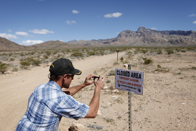 Mel Bundy, son of Cliven Bundy, takes a picture of a temporary closure sign on federal land 80 miles northeast of Las Vegas Tuesday, April 1, 2014. Cliven Bundy runs cattle on the land. The Bureau ...