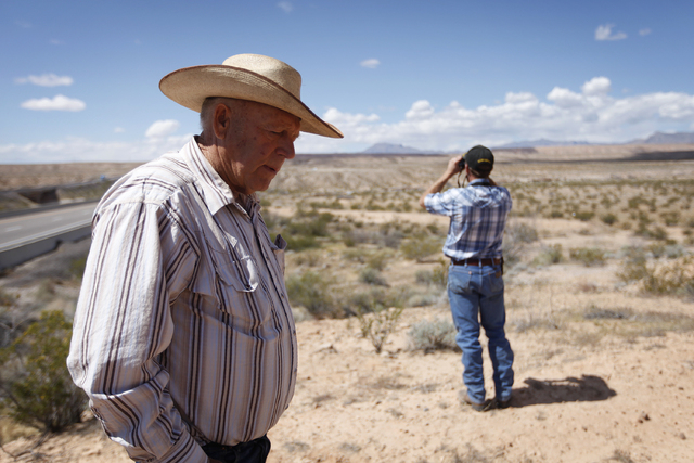 Cliven Bundy, left, and his son Mel bunny stand on a hill overlooking an area where federal authorities are building corrals near Bunkerville, Nev. Tuesday, April 1, 2014. Cliven Bundy runs cattle ...