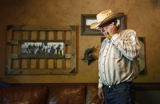 Cliven Bundy speaks on a phone in his home near Bunkerville, Nev. Tuesday, April 1, 2014. The Bureau of Land Management has been closing off the Gold Butte area near Bunkerville in preparation to  ...