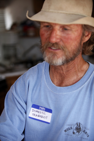 "Thomas Firth wears a badge that says ""domestic terrorist"" in his RV at a protest camp near Bunkerville, Nev. Friday, April 18, 2014. (John Locher/Las Vegas Review-Journal)"