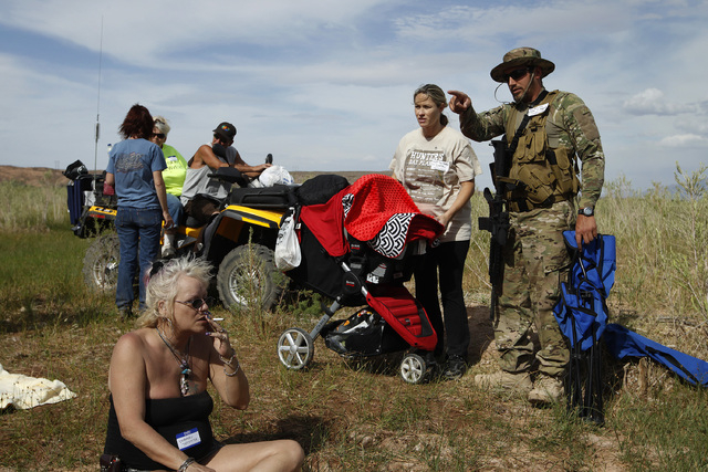 Steven Scalzo, right, and his wife Jamie Scalzo look for a place to set up their chairs during a rally in support of Cliven Bundy along the Virgin River near Bunkerville, Nev. Friday, April 18, 20 ...