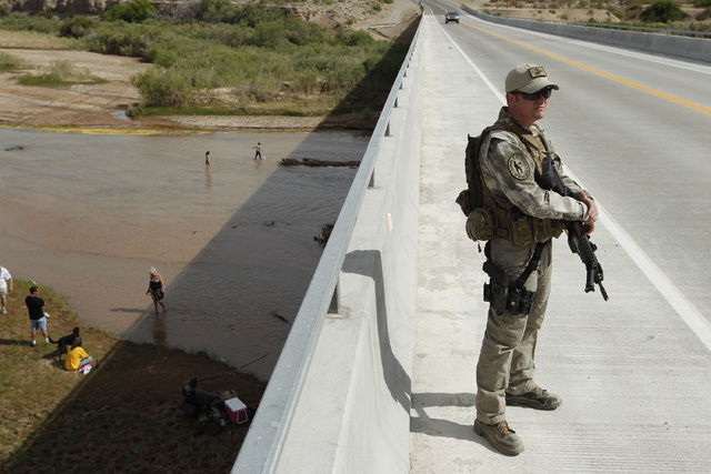Justin Giles of Wasilla, Alaska stands on a bridge over the Virgin River during a rally in support of Cliven Bundy near Bunkerville, Nev. Friday, April 18, 2014. (John Locher/Las Vegas Review-Journal)
