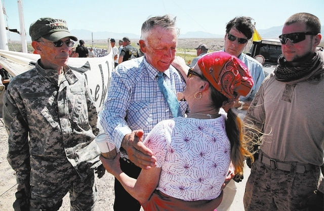 Rancher Cliven Bundy, center, greets Michelle Arnett, of Bullhead City, Ariz. near Bundy's ranch in Bunkerville on Sunday, April 13, 2014. Flanking Bundy are Jay Laduc, left, a member of the Minut ...