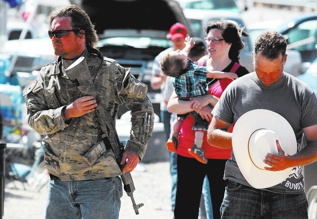 An armed man attends a ceremony near Cliven Bundy's ranch in Bunkerville on Sunday, April 13, 2014. Bundy and the Bureau of Land Management  reached a deal to stop the cattle roundup on Saturday.  ...
