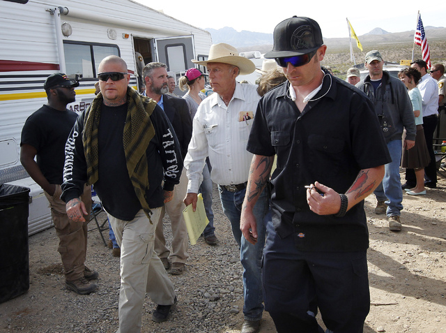 Rancher Cliven Bundy, middle, is escorted by security personnel to speak in front of his supporters at a rally site outside of Bunkerville on Saturday morning, April 12, 2014. (Jason Bean/Las Vega ...