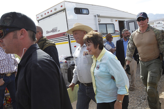 Rancher Cliven Bundy, middle, and his wife Carol are escorted by security personnel to speak in front of their supporters at a rally site outside of Bunkerville on Saturday morning, April 12, 2014 ...