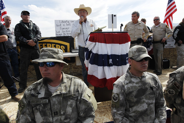 Rancher Cliven Bundy, middle, addresses his supporters alongside Clark County Sheriff Doug Gillespie, right, on April 12, 2014. Bundy informed the public that the BLM has agreed to cease the round ...