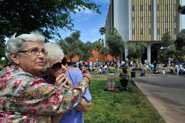 """Carol Willmann, left, consoles her friend, Cookie Brinkmeyer, who recently lost her husband,  as the two watch a butterfly fly away during annual the Nathan Adelson Hospice's """"Celebration of  ..."""