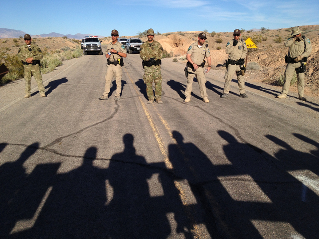 Bureau of Land Management law enforcement officers block the Overton Beach Road at the Lake Mead National Recreation Area near Overton, Nev. Thursday, April 10, 2014, as protestor's shadows are se ...