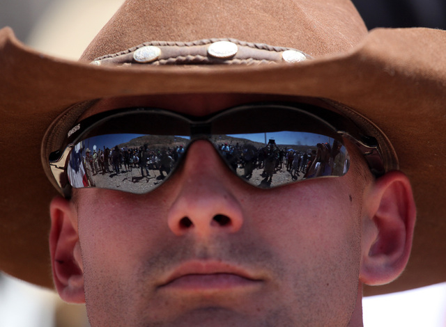 Darin Stanley, of St. George, Utah, stands guard in front of Cliven Bundy during a press conference at the protest camp near Cliven Bundy's ranch in Bunkerville on Monday, April 14, 2014. (Justin  ...