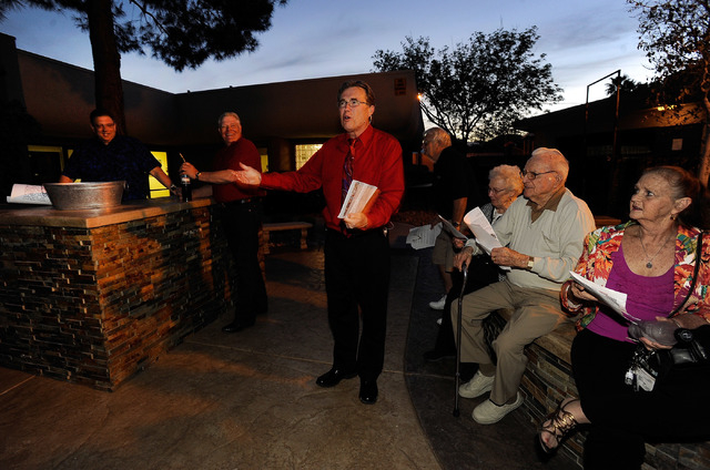 Pastor Bill Phillips, center, leads his congregation before two oversized copies of the church's mortgage were burned during a ceremony at Christ Lutheran Church on Sunday, March 23, 2014. The Las ...