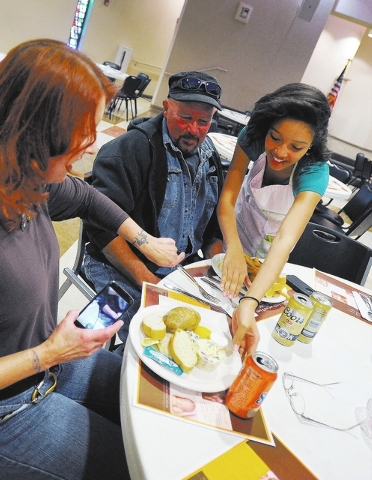 Kiara Barrios, right, serves plates of fish and potatoes to Lyn Bates, left and Scott Anderson during the weekly fish fry at St. Viator Catholic Church on Friday, March 28, 2014. (David Becker/Las ...