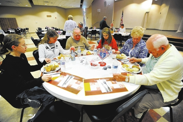 Diners from left, Amelia Davis, Diane Davis, George Mullen, Christa Davis, Delores Davis and Joe Carr say grace together before eating during the weekly fish fry at St. Viator Catholic Church on F ...