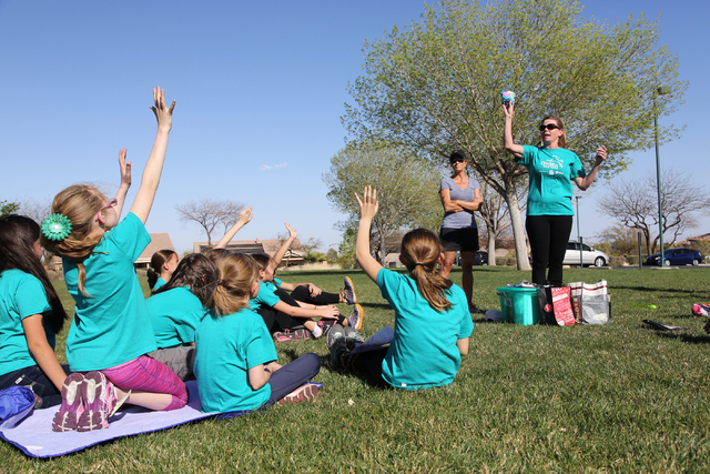 Coach Teri Heinz throws a plush fish used to signify whose turn it is to speak during a Girls on the Run workout at Tree Top Park. (Alex Federowicz/View)