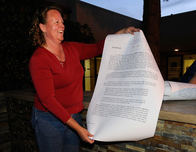 Church council member Kate Sorom displays an oversized copy of the church's mortgage before it  was burned during a ceremony at Christ Lutheran Church on Sunday, March 23, 2014. The church receive ...