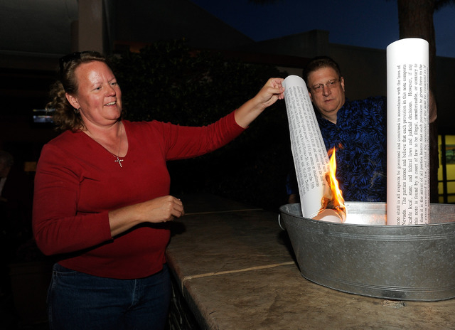 Church council member Kate Sorom, left and Jon Linker watch as two oversized copies of the church's mortgage begin to burn during a ceremony at Christ Lutheran Church on Sunday, March 23, 2014. Th ...