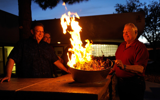 Church council member Jon Linker, left, pastor Bill Phillips and church council member Al Nerland watch as two oversized copies of the church's mortgage burn during a ceremony at Christ Lutheran C ...