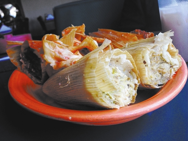 The larger than normal green tamales, front, are made with shredded chicken in a hot sauce, and the red tamales, back, are made from pulled pork in a mild sauce. (Sandy Lopez/View)