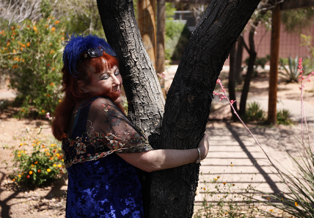 Annie Sprinkle hugs a tree while leading the Ecosex walking tour through UNLV in Las Vegas Wednesday, April 23, 2014. (John Locher/Las Vegas Review-Journal)