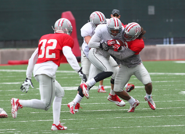 UNLV running back Adonis Smith pushes through an unidentified player during spring practice at Rebel Park at the University of Nevada, Las Vegas on Wednesday, April 2, 2014. (Chase Stevens/Las Veg ...