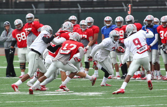 UNLV senior running back Adonis Smith, center, carries during spring practice Wednesday at Rebel Park. Smith, a 2012 transfer from Northwestern, is among four running backs competing to seize the  ...