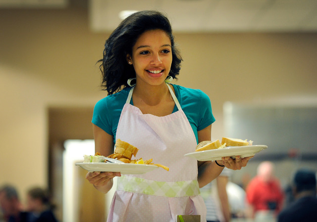 Server Kiara Barrios delivers plates to diners during the weekly fish fry at St. Viator Catholic Church on Friday, March 28, 2014. (David Becker/Las Vegas Review-Journal)